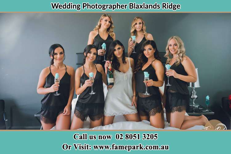 The bride holding a bottle of wine poses with the girls in front of camera Blaxlands Ridge NWS 2758