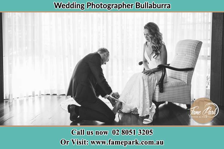 The Bride is being helped by the Groom trying to put on her shoes Bullaburra NSW 2784