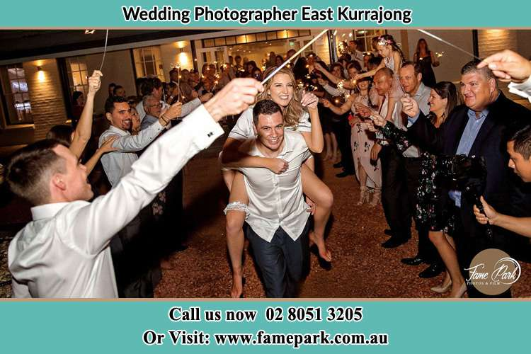 The Groom carrying her Bride while while the crowd cheering them East Kurrajong NSW 2758