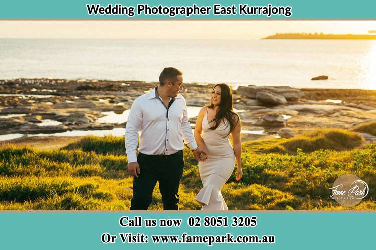 Photo of the Groom and the Bride walking near the shore as they look at each other East Kurrajong NSW 2758