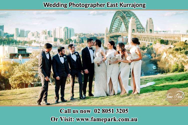 Photo of the Groom and the Bride kissing near the bridge while being watched by their entourage East Kurrajong NSW 2758