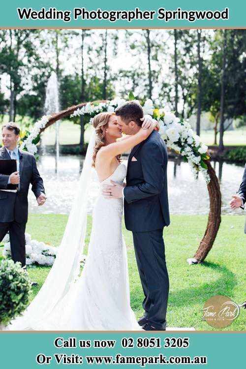 Photo of the Bride and the Groom kiss at the wedding ceremony Springwood